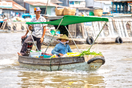 vietnamese ethnicity: Can Tho, Vietnam - April 5th, 2015: Spouses boating on the river trade vegetables at the floating market in Can Tho morning, Vietnam