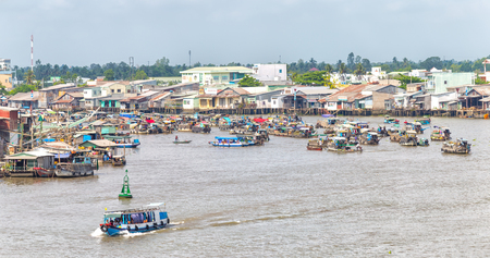 rang: Can Tho, Vietnam - April 5th, 2015: Village floating market on river junction with houses along river, across agricultural market place with boat carrying vegetables this place bustling trade in morning in Can Tho, Vietnam
