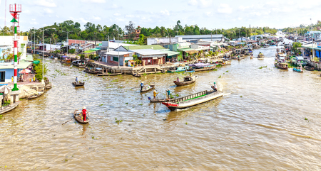 vietnamese ethnicity: Hau Giang, Vietnam - April 6th, 2015: Close down corner floating market river with boats, ships filthy beats back and forth on the river, the boat ferryman, boats carrying agricultural products are all gathered in Hau Giang, Vietnam Editorial
