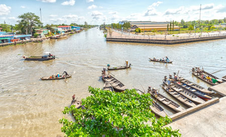 vietnamese ethnicity: Hau Giang, Vietnam - April 6th, 2015: Panorama wharf floating market with many boats gathered waiting passenger to the river, far away was the passenger barge across the river to go in the morning floating market in Hau Giang, Vietnam Editorial
