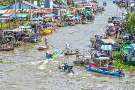 commodities: Hau Giang, Vietnam - April 6th, 2015: Macrofloating market on confluence with boats, canoes and transportation of agricultural products, fruits and vegetables, two riverside marina is focused agricultural commodities, all a river bustle of Hau Giang, Viet