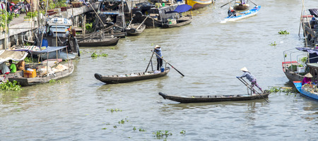 vietnamese ethnicity: Hau Giang, Vietnam - April 6th, 2015: Scenes of women rowing freight, bringing people across the river into the market early in Hau Giang, Vietnam