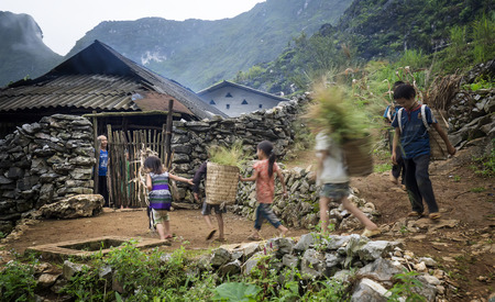 ha giang: Ha Giang, Vietnam - September 20th, 2015: The old father picked the children come home from work after a hard working day inside the small house on autumn afternoon in rocky plateau of Dong Van, Ha Giang, Vietnam Editorial