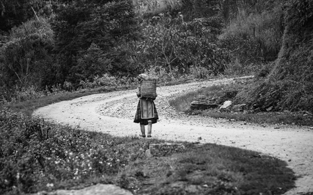livelihoods: Ha Giang, Vietnam - September 23rd, 2015: a woman is shipper peoples home on winding dirt road on autumn morning in Ha Giang, Vietnam Editorial