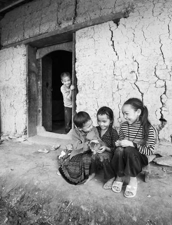 bebes niñas: Lao Cai, Vietnam - Septiembre 27 de, 2015: Los niños de las minorías étnicas se ríen con el gato en la mano en la tarde de otoño en Lao Cai, Vietnam