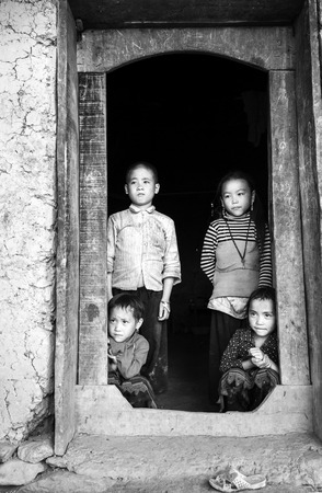 vietnamese ethnicity: Lao Cai, Vietnam - September 27th, 2015: the eyes of the children of farming parents waiting in the doorway of the house made of soil in autumn afternoon in rural mountainous area of Lao Cai, Vietnam