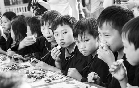 vietnamese ethnicity: Yen Bai, Vietnam - September 25th, 2015: Group of children are eating bread mid-autumn festival nets in Hoang Su Phi village in autumn afternoon in Yen Bai, Vietnam