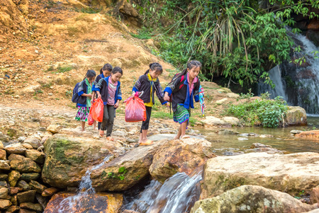 In Yen Bai, Vietnam - September 25th, 2015: A group of ethnic children are walking mountain stream crossing to attend school in the afternoon fall in Yen Bai, Vietnam