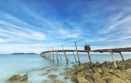Photographic inventory of the wooden bridge with blue sky, long wooden bridge and smooth water surface distance is truly idyllic mountain ... for a summer afternoon while hunting Photo Stock Photo