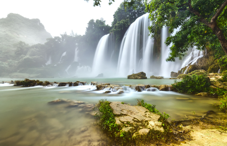 Ban Gioc Waterfall flickers inside the canopy with the path pedestal foot waterfall flowing waters to create rapids for the soft mist splashed through beautiful Stock Photo