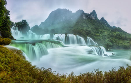 stratification: Ban Gioc Waterfall craggy limestone misty morning permissive side with foreground grass and tones of the lower cascade. Considered the most beautiful It is in Southeast Asia and Waterfalls is a national scenic Vietnam