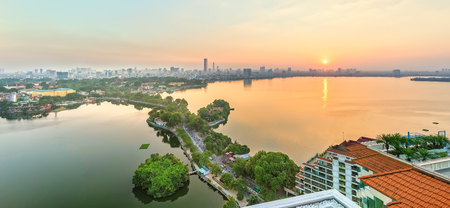 Hanoi, Vietnam, September 28, 2015: Panorama West lake sunset horizon khi where skyscrapers sun go down, still lake, green path through small idyllic island beauty t?o watching in Hanoi, Vietnam Editorial