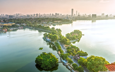 The road crossing the island Westlake, Hanoi, Vietnam with tree-lined streets green, small temples located gi?a oasis in sunshine of the West Lake and boasts a beautiful evening in capital of Vietnam