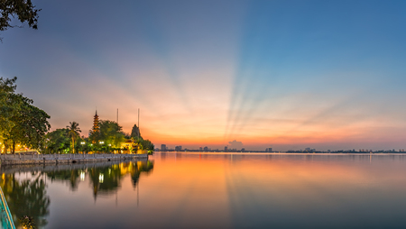 Hanoi, Vietnam - September 28th, 2015: Tran Quoc Pagoda lake west side Sunray welcomed with pink rays sky Makes the sunset sky as a theatrical dance in Hanoi, Vietnam Editorial