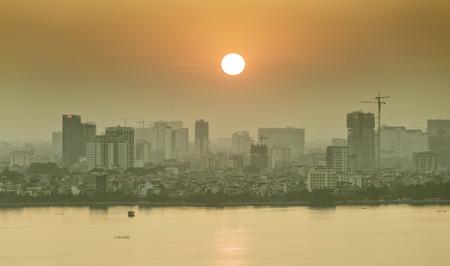 riverbank: Hanoi, Vietnam, September 28th, 2015: Sunset on West Lake with big sun, rounded downward ineffable city skyline Stillness Makes peaceful sleep in Hanoi, Vietnam
