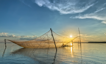 livelihoods: Dong Nai, Vietnam - November 15th, 2015: The Fishermen are mending nets as patch Implied HIS life in autumn afternoon in Tri An, Dong Nai, Vietnam Editorial