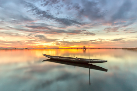 serenety: Lonely boat lake with beautiful sunset sky gi?a bright yellow dimensional horizon, the largest lagoon in central Vietnam this the subject of art for artists to come here khi c? composing a chance. Stock Photo