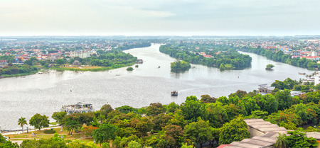 poetic: Peaceful scenery on the river with boat glides on water, houses with red tile small distance roofs, river turn right back from making a painting of Hue Ancient Capital Poetic today