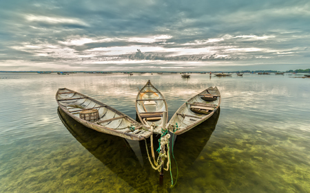 Three boats together to welcome the new day Reflected the still lake, far away is the Fishermens boats around Tam Giang lagoon nomadic. Shui wood painting meaningful in life