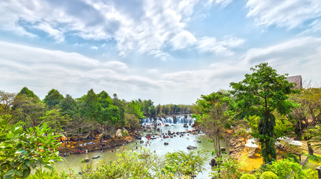 Giang Dien Waterfall seen from above with water pouring down billowing white, surrounded by a forest covered many tourists to the resort Attract, above the beautiful cloudy sky sunny day freshness fresh welcome Stock Photo