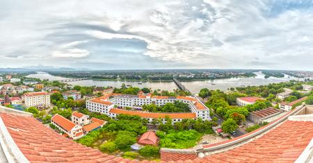 Hue, Vietnam - 21 giugno 2015: Hue città in un pomeriggio estivo tramonto panorama con un ponte sulla costa che collega il sud e il nord. Questa è un'antichità della città turistica, i turisti sono attratti da quattro direzioni nostalgiche. L'architettura del tetto è stata conservata per