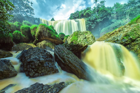 silt: Elephant Falls on a summer afternoon with old plaster stone structure, water, splashing, yellow water contains silt Due basaltic soils here are Considered from beautiful natural waterfall of Lam Dong Stock Photo