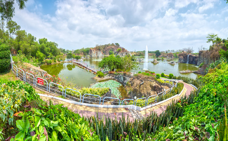 interspersed: Dong Nai, Vietnam - February 23rd, 2015: Panorama mountain lake with bridges crossing paths dragon island interspersed Vegetation rich landscape around this place more beautiful, idyllic to welcome spring in Dong Nai, Vietnam Editorial