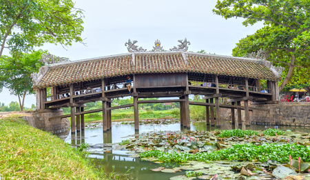 Thua Thien Hue, Vietnam - June 21st, 2015: Architecture bridge with wooden roofing tiles on like a house on structures to Attract tourists to relax river, below lilies blooming beauty idyllic countryside t?o in Thua Thien Hue, Vietnam