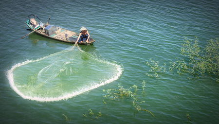 commercial fishing net: Dong Nai, Vietnam - November 15th, 2015: The Fishermen casting nets to catch fish Improves a better life circle in the winter morning at Tri An, Dong Nai, Vietnam. This is the daily work of labor but Expressed beauty