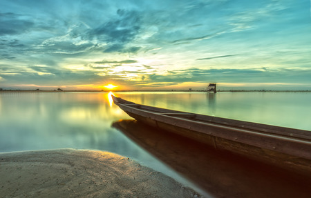 serenety: The boat speeding Toward the sun as if to hold back the light at sunset while the sun shines bright yellow rays radiating below the surface smooth like smoke. Competent competent in dramatic paintings in lyricism. Stock Photo