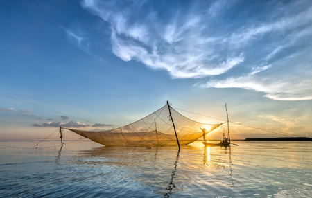 livelihoods: Dong Nai, Vietnam - November 15th, 2015: Fishermen mending nets on his net lift lifetime to grow as more patch in the autumn afternoon in Tri An, Dong Nai, Vietnam Editorial