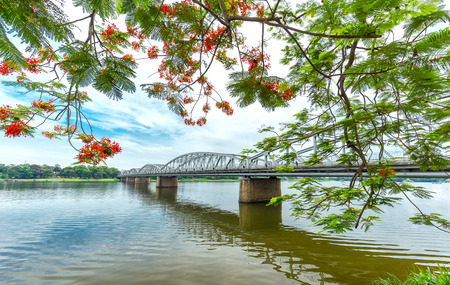 Trang Tien Bridge looming flamboyant branches reflecting on the river side. This is a classic symbol of Hue photo corners