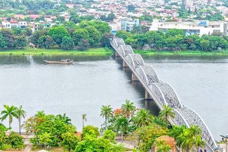 clearer: Hue, Vietnam - June 21st, 2015: Trang Tien Bridge Douple connecting the waterfront with boat passing Hue Perfume giving Poetic painting. Photos taken from high above the landscape is Clearer in views.