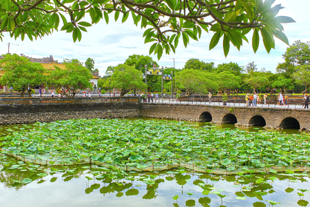 Hue, Vietnam - July 16th, 2011: Lotus Pond in the Forbidden City of Hue with architecture bastion in the middle as in many handheld They were beauty attracts tourists create, it is world-cultural heritage nh?n old Editorial