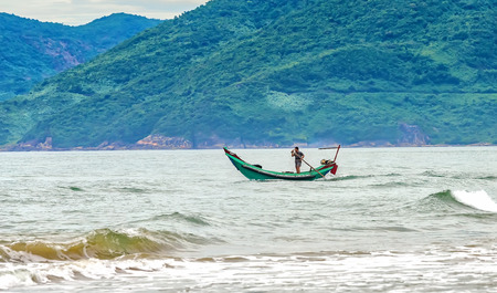 Thua Thien Hue, Vietnam - June 23rd, 2015: Fishermen out to sea in boats with curved nose morning as if to confront big waves offshore, although hard, but much improved results seas fishing income for People in Thua Thien Hue, Vietnam biên tập