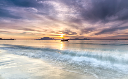 Doc Let beach Dawn on the waves pounding the shore with the distance is small boat in welcome sunshine greet the new first day. Stock Photo
