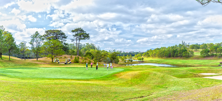 interspersed: Lam Dong, Vietnam - February 4th, 2015: A family playing golf under vast green valley pastures where pine forests interspersed, fresh water lake really cool, to enjoy holidays in Lam Dong, Vietnam