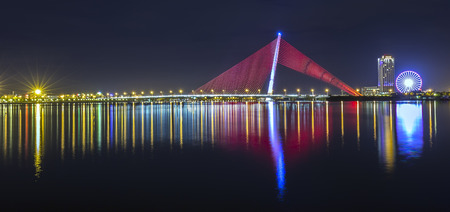 Da Nang, Vietnam - 25th June, 2015: architectural beauty of light a sail shaped mirror Tran Thi Ly Bridge shimmering Into the river at night create the beauty of the city of Da Nang, Vietnam Tran Thi Ly Bridge, Da Nang nightlife with shining lights Editorial