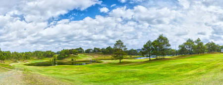 Lam Dong, Vietnam - February 4th, 2015: Panorama Golf Dalat pine forest with broad lawns inside hill, golfers roll over small bridge above beautiful clouds create vivid sky in Lam Dong, Vietnam