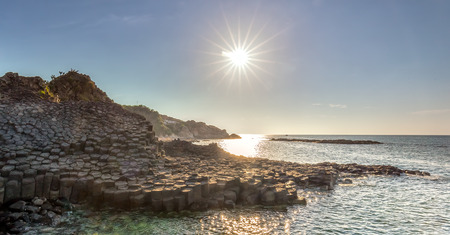 Morning sun shining on Giant Causeway khi Sunstar radiating down on stone fly as a national landmark is recognized companies, this place attracts tourists to relax and explore