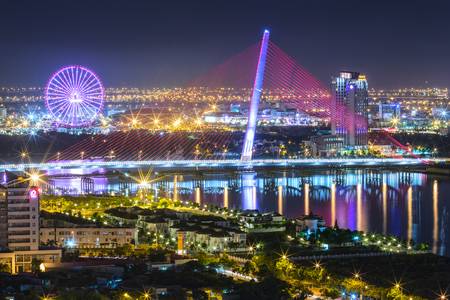 Da Nang, Vietnam, 25th June, 2015: The beauty architecture with the sail bridge at night lights of the bridge shaped sails shimmering beneath the city lit up at night Makes the city more lively in Danang, Vietnam