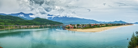 Lang Co Bay panorama with cloud cover sheet Underneath bridges crossing dragon fly fine sand beach, calm water, small inshore fishing boat drifting quietly very Poetic in Hue, Vietnam Standard-Bild