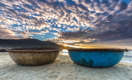 Da Nang, Vietnam, June 26, 2015: Sunrise over seaside with sunlight to create stars and double Pannier foreground boat, exercising and watching ng??i Fishermen bring fish on sale in Da Nang, Vietnam Stock Photo