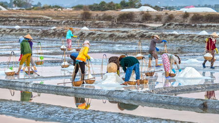 Khanh Hoa, Vietnam, Farmers pour salt in the salt fields with the bent shoulders pour salt Into the collecting basket and carry ashore, all the hardships c%uFFFD make up the beauty of labor Farmers Khanh Hoa, Vietnam