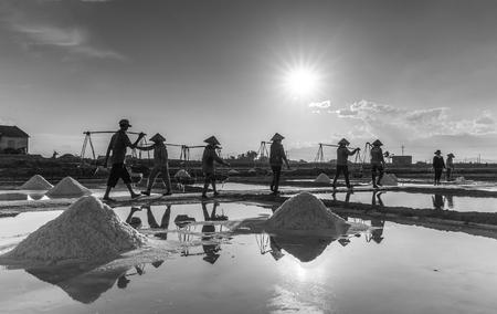 Khanh Hoa, Vietnam, June 30, 2015: Farmers Group salt salt salt pans on the burden on Summer Afternoons Jimmy sun is down gradually khi Hon Khoi salt in the field, Khanh Hoa, Vietnam