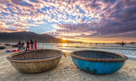 Da Nang, Vietnam, June 26, 2015: Sunrise over seaside with sunlight to create stars and double Pannier foreground boat, exercising and watching ng??i Fishermen bring fish on sale in Da Nang, Vietnam Editorial