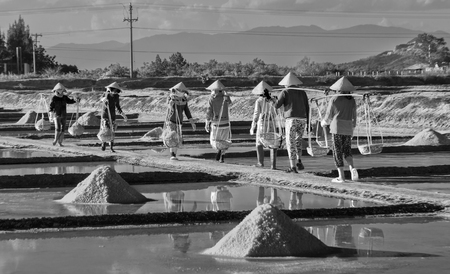 Khanh Hoa, Vietnam, June 30, 2015: Group of salt is salt in the salt Farmers bear on a summer afternoon pans Hon Khoi salt uh, Khanh Hoa, Vietnam