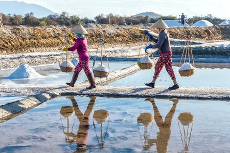 livelihoods: Khanh Hoa, Vietnam, June 30th, 2015: Farmers Carrying salt on embankment with full shoulders the burden hurried mirror alignment salt water Into create beauty peasant labor in Khanh Hoa, Vietnam