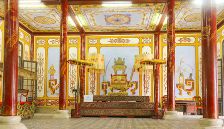 reigns: Hue, Vietnam - July 16th, 2011: Palace of Forbidden City in Hue with red lacquer trimmed with Palatial architecture gold, Throne King reigns center court sat l� khi assembly feudal state power. It nh?n national cultural heritage Editorial
