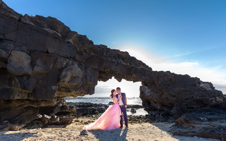 Ly Son Island, Vietnam, June 27th, 2015: Couple happy with stone gate on flying khi afternoon sun gradually to create a halo behind highlighters enjoying holiday island Wilderness